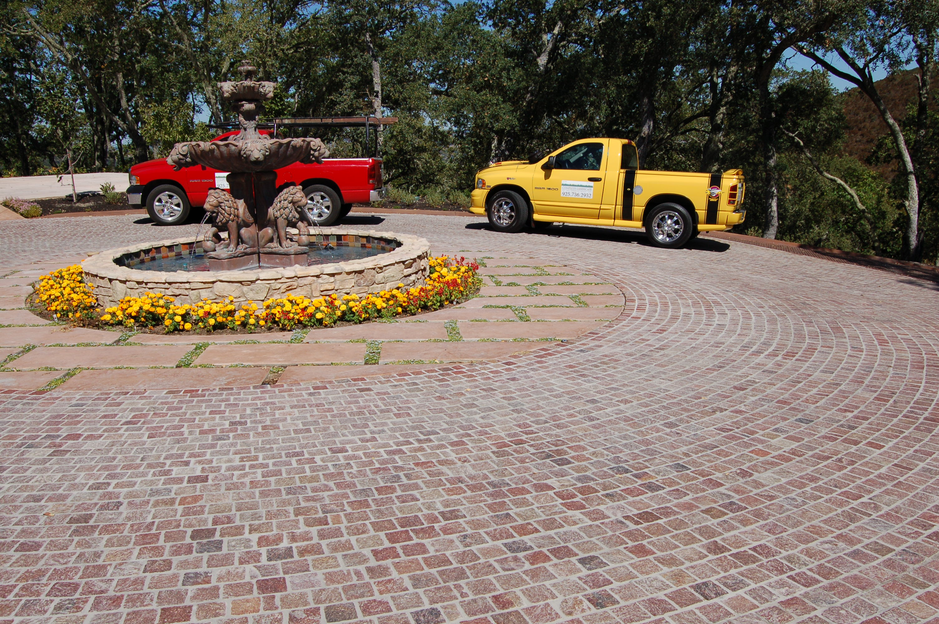 Finished driveway featuring a running bond pattern in Copper Mountain Porphyry around a circular fountain